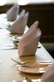 Dining table setting. A dining table with a folded napkin and plates with fork and spoon Stock Photos