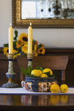 Dining table still life. Antique bowl filled with fresh lemons, antique Doulton Lambeth candlesticks and fresh flowers in background stock photos