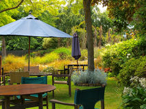 Dining table in sunny garden. Patio with sunshade Stock Image