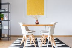 Dining table on triangle carpet Royalty Free Stock Image