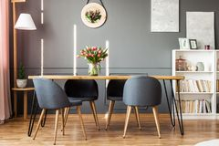 Dining table and tulips. Wooden dining table, grey chairs, bookshelf and pink tulips in dining room interior royalty free stock photos