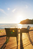 Dining table and two chairs on decking by sea side at evening su Royalty Free Stock Photos
