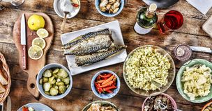 Dining table with a variety of snacks and salads. Salmon, olives, wine, vegetables, grilled fish toast. The concept of a family ce. Lebratory dinner royalty free stock photography