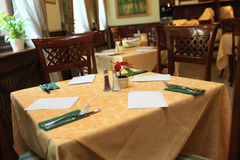 Dining table with yellow cloth Royalty Free Stock Photos