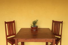 Dining table with yellow wall Stock Photo