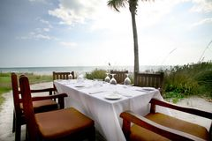 Dining on the water. A place setting for four guest at a Naples, Florida Gulf of Mexico restaurant stock photo