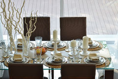 Dining wooden table in modern home with elegant table setting Royalty Free Stock Photos
