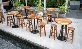 Dining wooden tables with wooden chairs for dining out. On concrete floor stock images