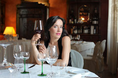Dinner. Beautiful woman holding a glass of wine Stock Photography