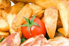 Dinner. Tasty fried potato wedges, tomato and pork dinner Royalty Free Stock Image
