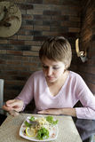 Dinner. The girl eating salad with green in restaurant Royalty Free Stock Photography