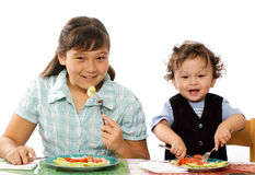 Dinner!. Two children have dinner,isolated on a white background Royalty Free Stock Image
