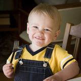 Dinner. Child ready for eating with fork in hand at dinner time stock photos