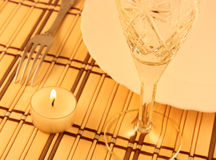 Dinner. Plate, fork and wineglass on a bamboo placemat Stock Photos