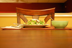 Dinner from across the table. This is a shot of a dinner salad shot from across the table. the top of a chair, a dinner plate and bowl can be seen in the image Royalty Free Stock Image