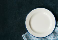 Dinner plate with napkin. Dinner background, plate and napkin on dark rustic table, top view with place for text royalty free stock photography