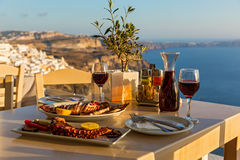 Dinner on the background of sea sunset. Dinner with seafood and red wine on the background of sea sunset Stock Images