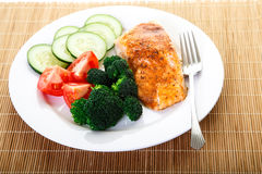 Dinner of Baked Salmon and Fresh Vegetables. A dinner of baked salmon, broccoli, tomatoes and cucumber Royalty Free Stock Image