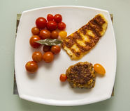 Dinner of beef patties grilled cheese and cherry tomatoes Royalty Free Stock Images