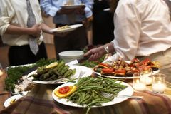 Dinner being served at a wedding. Food being served buffet style during a wedding event. This was shot witha slow shutter speed, and there is some movement Royalty Free Stock Images
