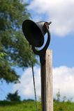 Dinner Bell. A dinner bell mounted on a post outside of the main farmhouse on an Amish farm in the heart of Ohio's Amish country Stock Photography