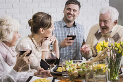 Dinner is better with family. Happy family sitting beside table during dinner, smiling Royalty Free Stock Photography