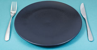 Dinner black plate with fork and knife on green Stock Photography