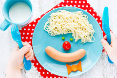 Dinner or breakfast for kids - clown face spaghetti with sausage Stock Photo