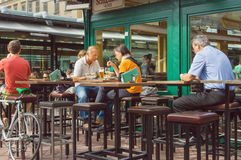 Dinner of busy people in outdoor city cafe with tall wooden tables and chairs Royalty Free Stock Images