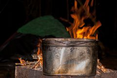 Dinner at the campsite. kettle on a burning fire, fire, smoke. preparing a meal on a trip. wild rest royalty free stock photography