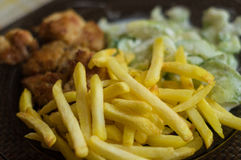 Dinner with chcken nuggets, chips and cucumber salad Stock Images