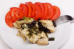 Dinner from chicken breast, prunes and tomatoes Stock Photos