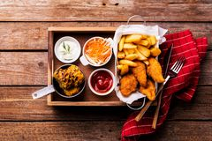 Dinner - chicken strips, french fries, roasted corn and salad. Country or rustic restaurant dinner - fried chicken strips, french fries, roasted corn, salad and royalty free stock image
