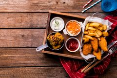Dinner - chicken strips, french fries, roasted corn and salad. Country or rustic restaurant dinner - fried chicken strips, french fries, roasted corn, salad and stock images