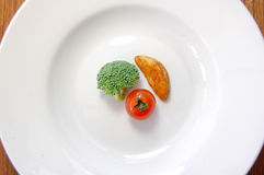 Dinner concept. Small portion of food on a big plate Stock Photo