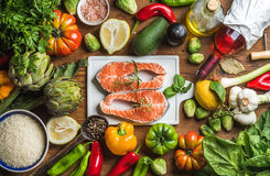 Dinner cooking ingredients. Raw uncooked salmon fish with vegetables, rice, herbs, lemon, artichokes, spices and bottle Royalty Free Stock Image