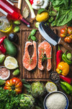 Dinner cooking ingredients. Raw uncooked salmon fish with vegetables, rice, herbs, lemon, spices and bottle of rose wine. Over rustic wooden board, top view Stock Photos