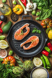 Dinner cooking ingredients. Raw uncooked salmon with vegetables, rice, herbs, lemon, artichokes, spices in iron grilling. Pan over wooden background, top view Stock Images