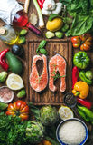 Dinner cooking ingredients. Two pieces of raw uncooked salmon fish with fresh vegetables, rice, herbs, lemon, spices Royalty Free Stock Photos