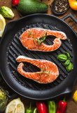 Dinner cooking ingredints. Raw uncooked salmon fish with vegetables, herbs and spices in iron grilling pan. Over rustic wooden background, top view Stock Images