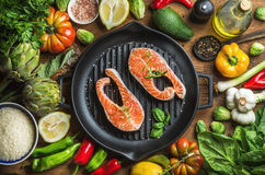 Dinner cooking ingredints. Raw uncooked salmon fish with vegetables, rice, herbs, spices and oil in iron grilling pan Royalty Free Stock Photo