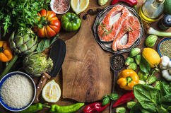 Dinner cooking ingredints. Raw uncooked salmon fish with vegetables, rice, herbs and spices over rustic wooden. Background, top view, copy space. Chopping board Stock Image