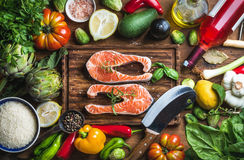 Dinner cooking ingredints. Raw uncooked salmon fish with vegetables, rice, herbs and spices. Over rustic wooden board, top view Royalty Free Stock Photography