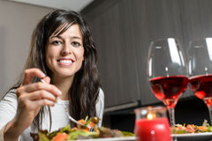 Dinner for couple. Pretty brunette woman sitting at the table smiling and eating a salad with a fork. Romantic dinner for a couple with candle and two glasses of Royalty Free Stock Photo
