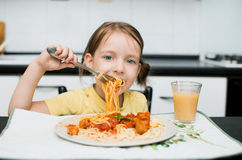 Dinner. Cute little girl eating spaghetti with tomato sauce and vegetables for dinner royalty free stock images