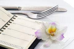Dinner Date. Diary glasses flower plate and knife and fork dinner date love concept Royalty Free Stock Photo