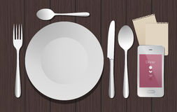 Dinner elements and smartphone. Table and Dishes with smartphone. Wooden background Royalty Free Stock Photography