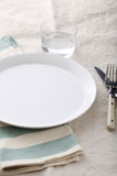 Dinner empty plate, fork, knife and glass water on the striped n Stock Photography