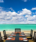 Dinner on exotic beach. Turquoise sea and cloudy blue sky Royalty Free Stock Images