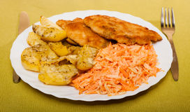Dinner. Fried chicken roasted potatos carrot salad Stock Image